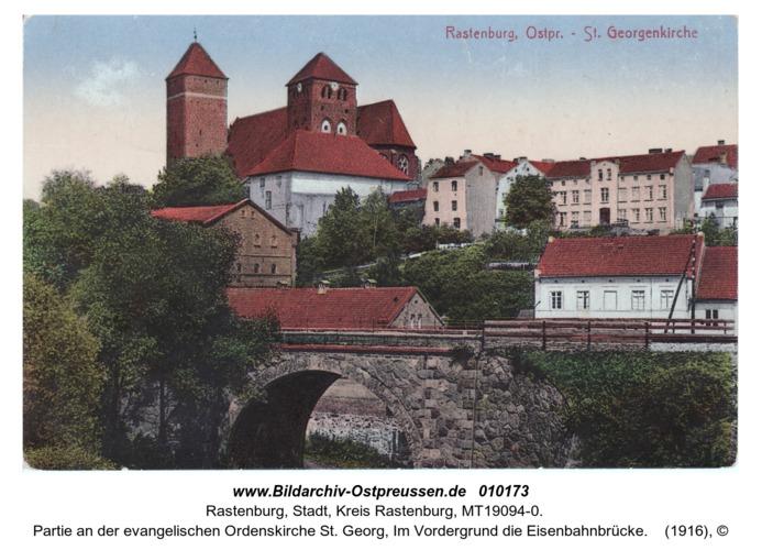 Rastenburg, Partie an der evangelischen Ordenskirche St. Georg, Im Vordergrund die Eisenbahnbrücke
